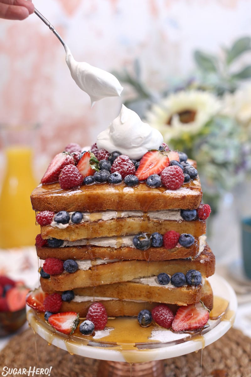 French toast cake with spoon putting a dollop of whipped cream on top