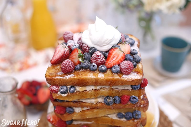 Close-up view of the French toast layer cake topped with fresh berries and whipped cream