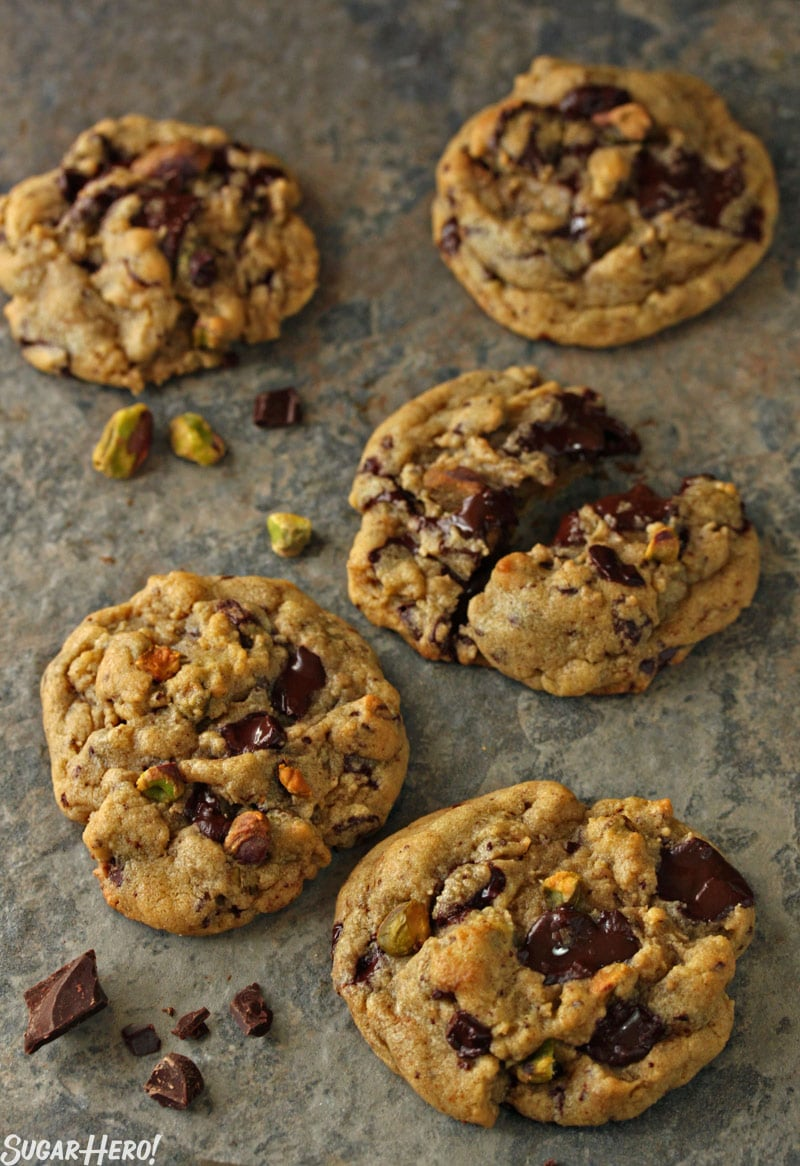 Pistachio Chocolate Chunk Cookies - Multiple cookies displayed with pistachios on the side. | From SugarHero.com