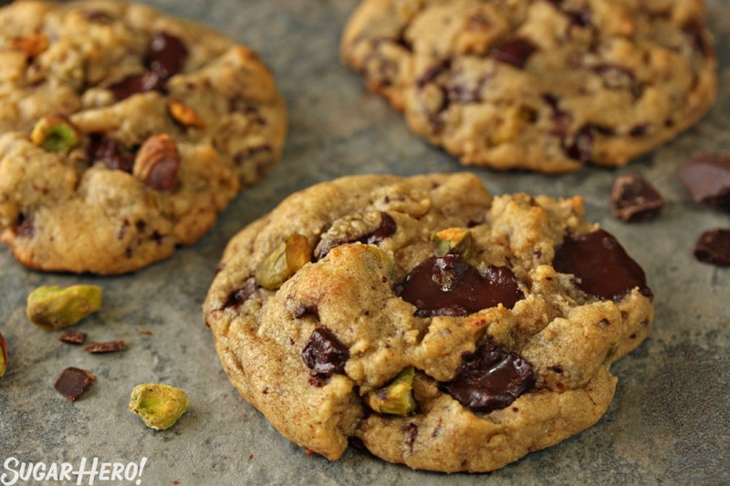 Pistachio Chocolate Chunk Cookies - A straight shot of a the cookies displayed with pistachios to the side. | From SugarHero.com