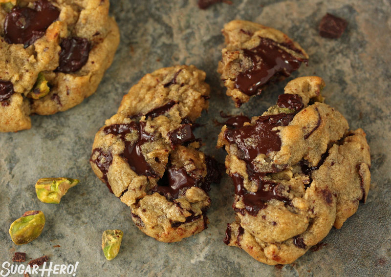 Pistachio Chocolate Chunk Cookies - A cookie split in half showing the chocolate chunks. | From SugarHero.com