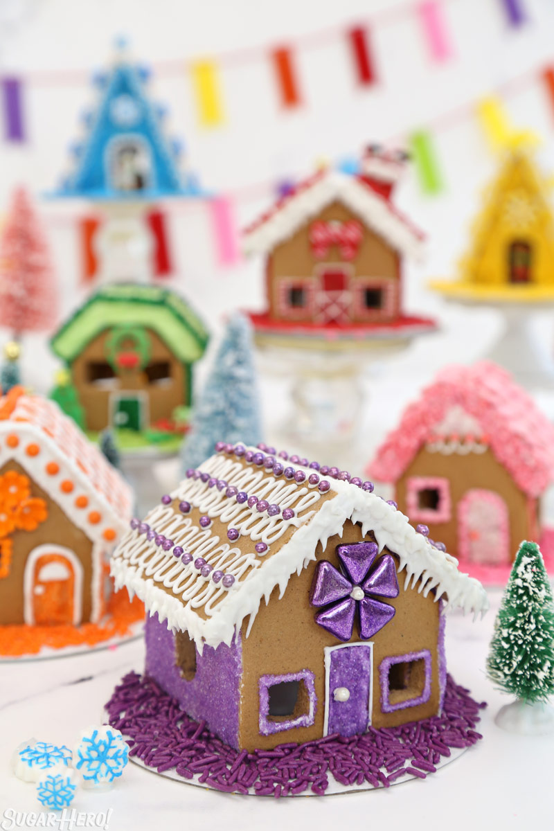 Miniature gingerbread houses decorated with rainbow colors | From SugarHero.com