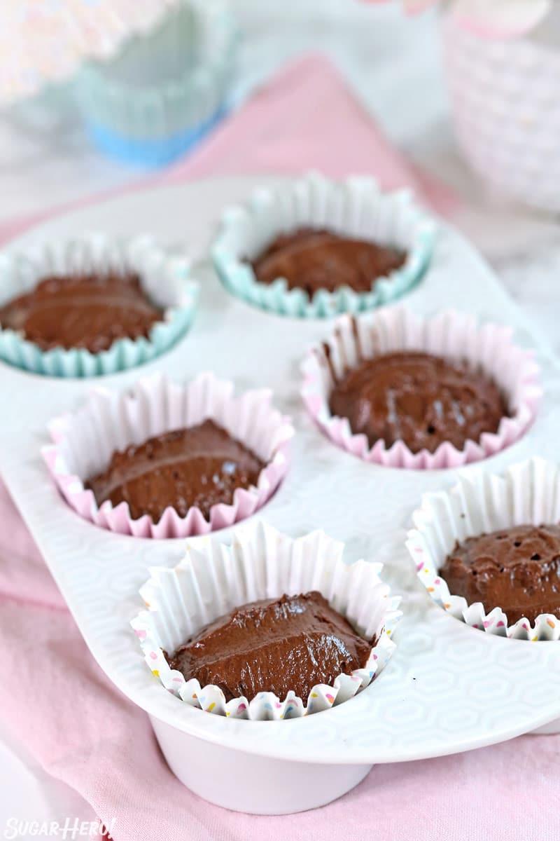 Cupcake pan filled with chocolate cupcake batter, before baking