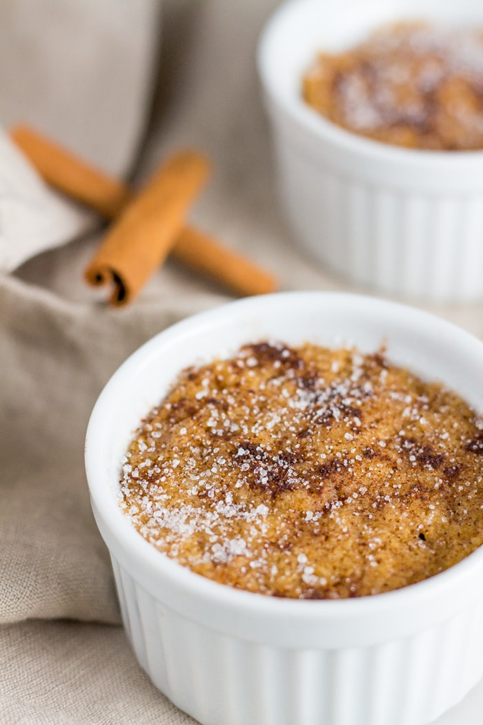 two snickerdoodle keto mug cakes with cinnamon sticks