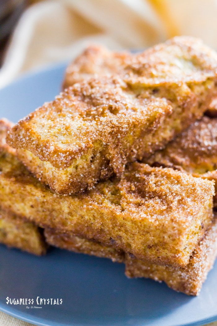 keto french toast sticks stacked on top of each other covered with sukrin brown sugar, cinnamon and granulated monk fruit