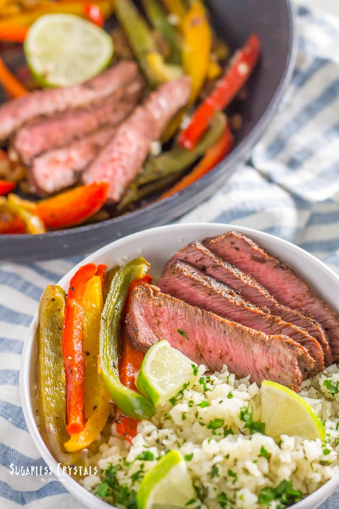 a pan of healthy steaks fajitas with a side bowl of cilantro lime cauliflower rice
