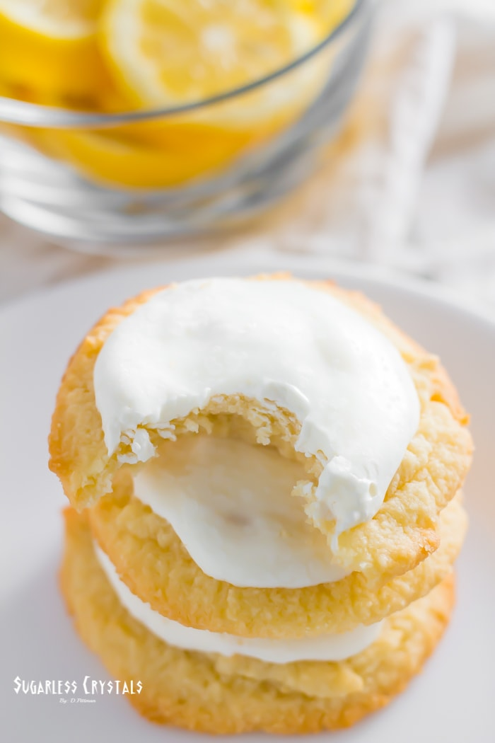 Lemon keto cookies stacked on one another with a bite taken out the top lemon keto cookie