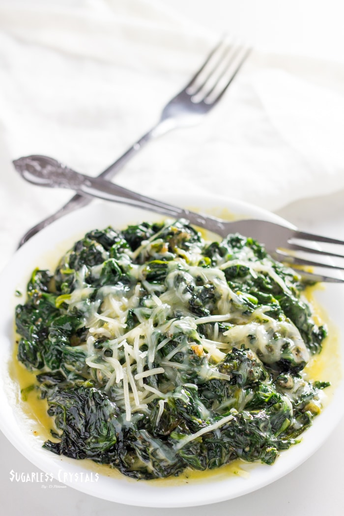 keto creamed spinach on a plate with parmesan cheese sprinkled on top