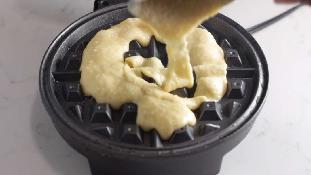 pouring batter on pre heated waffle maker