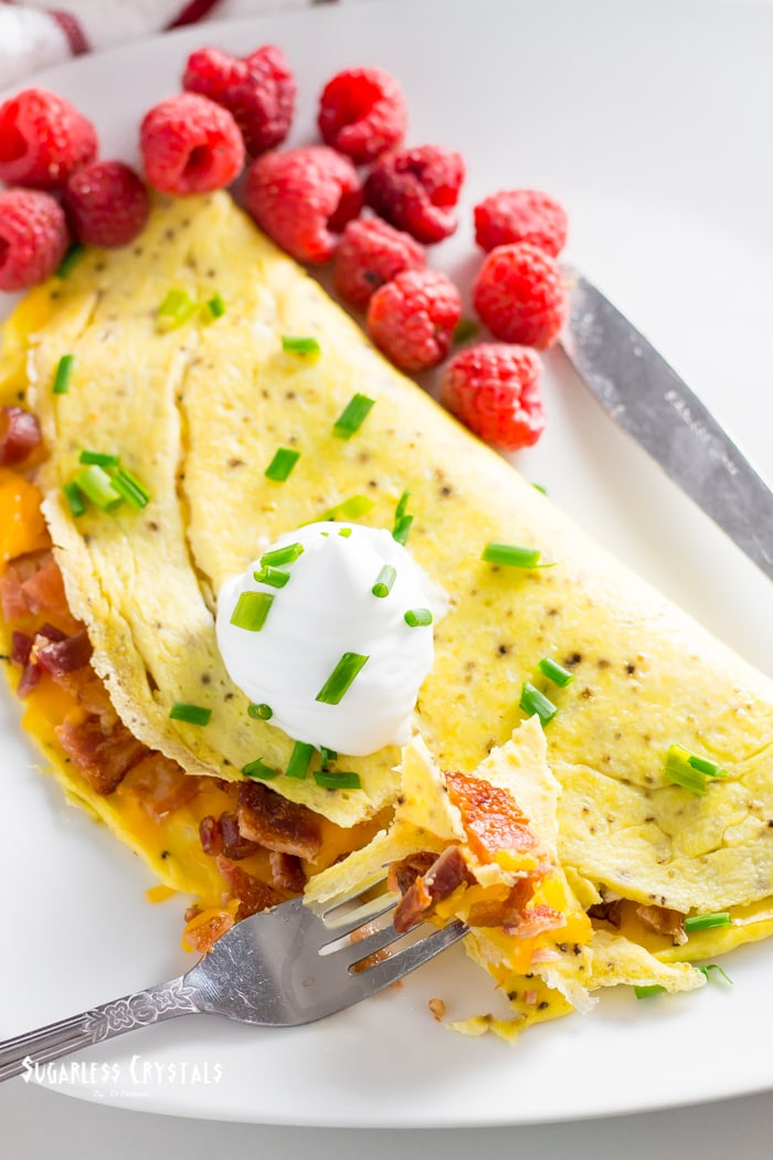 bacon keto omelette with raspberries, sour cream and chives