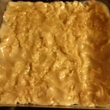 The cookie dough layer at the bottom of the pan.