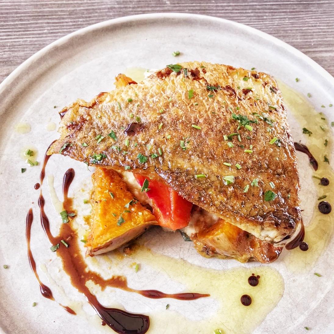Crispy Skin Barramundi with pesto tossed roasted vegetables, garlic yogurt and chickpea smash