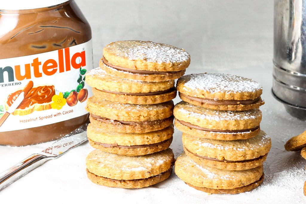 Hazelnut Shortbread Cookies with Nutella Filling. Perfect hazelnut shortbread cookies sandwiched together with a Nutella filling. These cookies are nothing short of amazing!