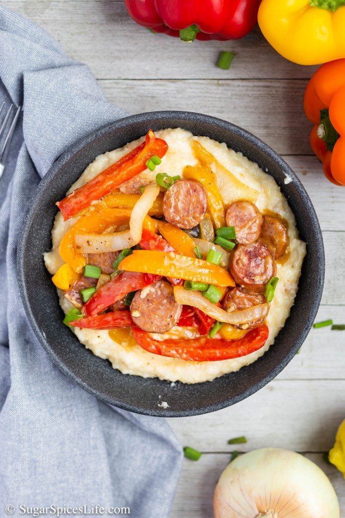This Sausage and Grits recipe has creamy, cheesy grits topped with sausage, bacon and vegetables in a delicious, lightly spicy sauce.