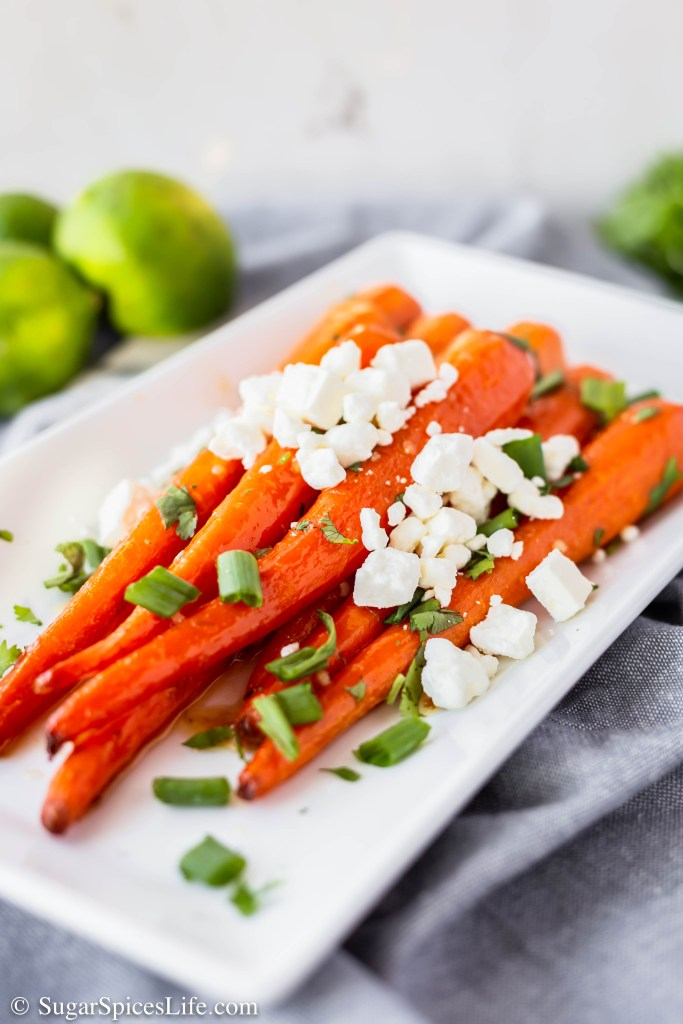 These Honey Lime Carrots have full sized carrots roasted in a honey, lime sauce until they're perfectly tender, and then topped with cheese, green onions, and cilantro. They taste like a carrot Mexican street corn.