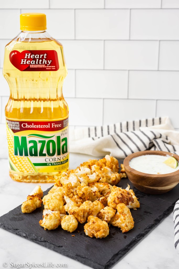 Cauliflower coated in deliciously seasoned rice flour, sprayed with Mazola corn oil, air fried to a perfect crisp, and then served with a lime yogurt dipping sauce. These Air Fried Cauliflower Poppers are a healthy, delectable snack or appetizer! #ChooseMazola #CollectiveBias #Ad