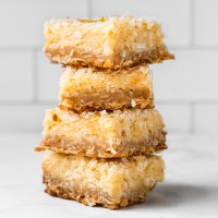 A lemon and oat pastry crust with a lemon butter filling and topped with toasted coconut. These Lemon Butter Bars are ooey gooey and jammed pack with lemon flavor!