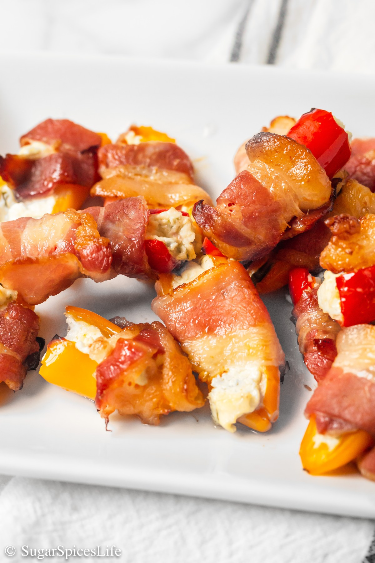 Mini sweet peppers filled with a chive onion cream cheese, then wrapped in bacon. Cooked in an oven, air fryer, or smoker, these Sweet Pepper Poppers are a perfect appetizer, side or snack!