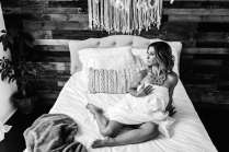 Doylestown Boudoir Photographer SugaShoc Photography lady on bed draped in sheet in black-and-white