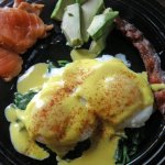 Eggs Hollandaise on a bed of Spinach with homemade Lox , fresh Avocado, and nitrate-free Bacon