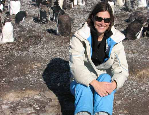 The author sitting with rockhopper penguins on Bleaker Island in the Falkland Islands.