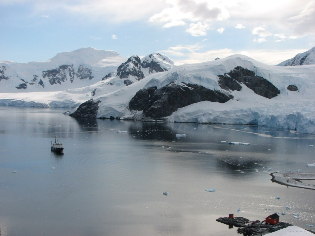 Pristine Paradise Harbour on the Antarctic Peninsula with our ship the Polar Pioneer moored in the background.
