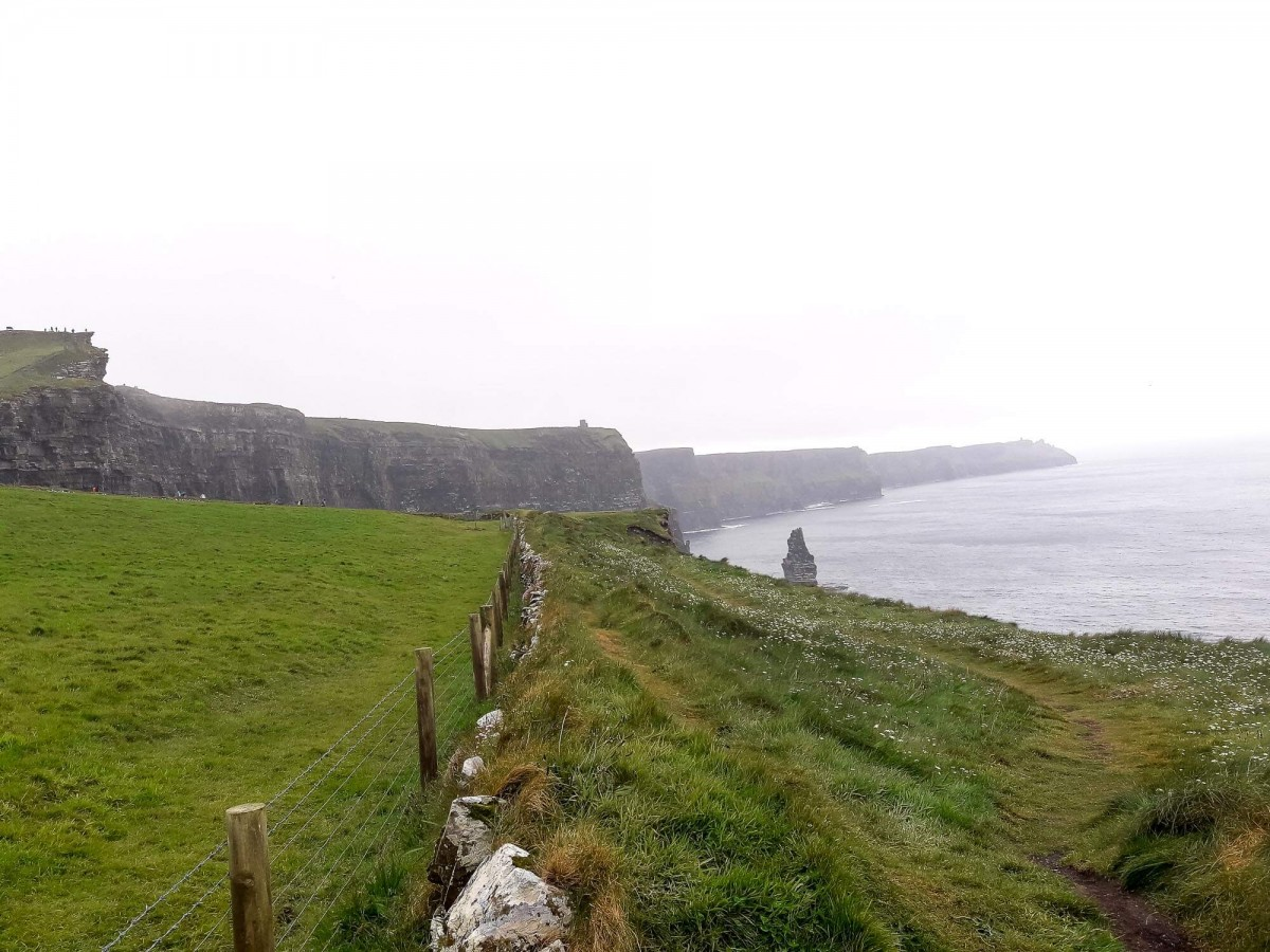 A barbed wire fence on the Doolin Hike lines the Cliffs of Moher