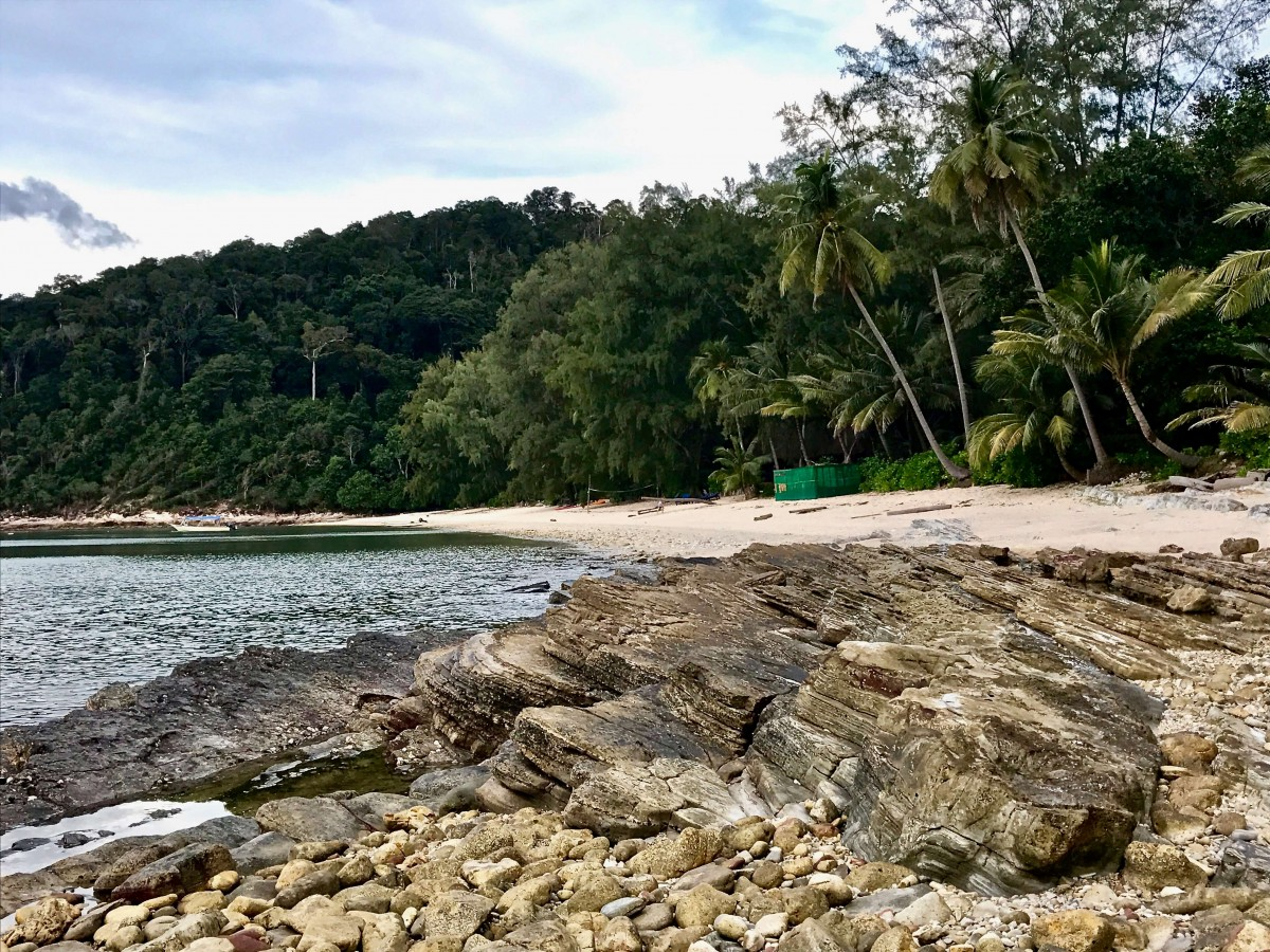stones and sand sit between the ocean and a wall of palm trees on the Rimba Resort beach