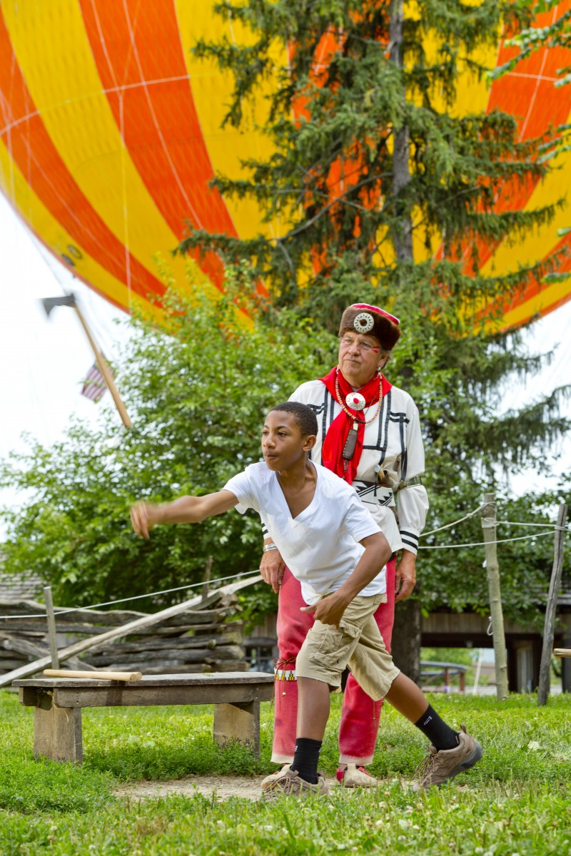 Photo courtesy of the Connor Prairie website, showing a child throwing an axe at one of their exhibits, in front of a giant hot air balloon.
