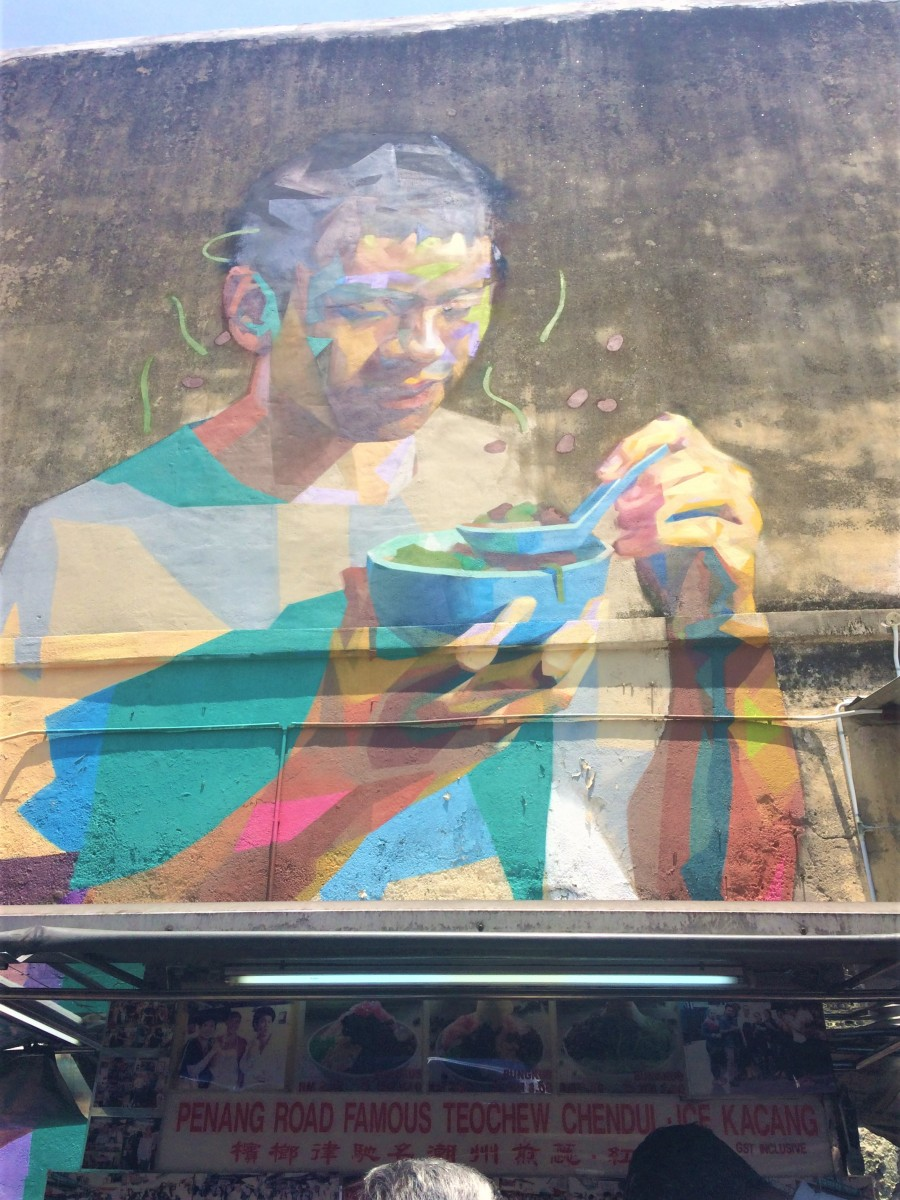 A wall mural of a man eating soup in Penang, wow Holly