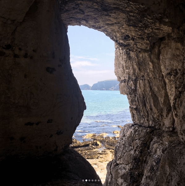 Lilly bridge - Picture of blue water and sand peaking through an opening in a rocky cave