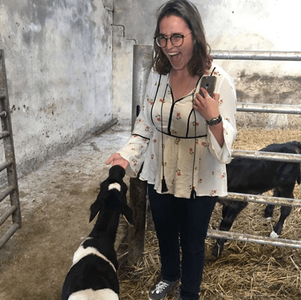 Picture of Lilly getting her fingers sucked by a small black and white cow calf