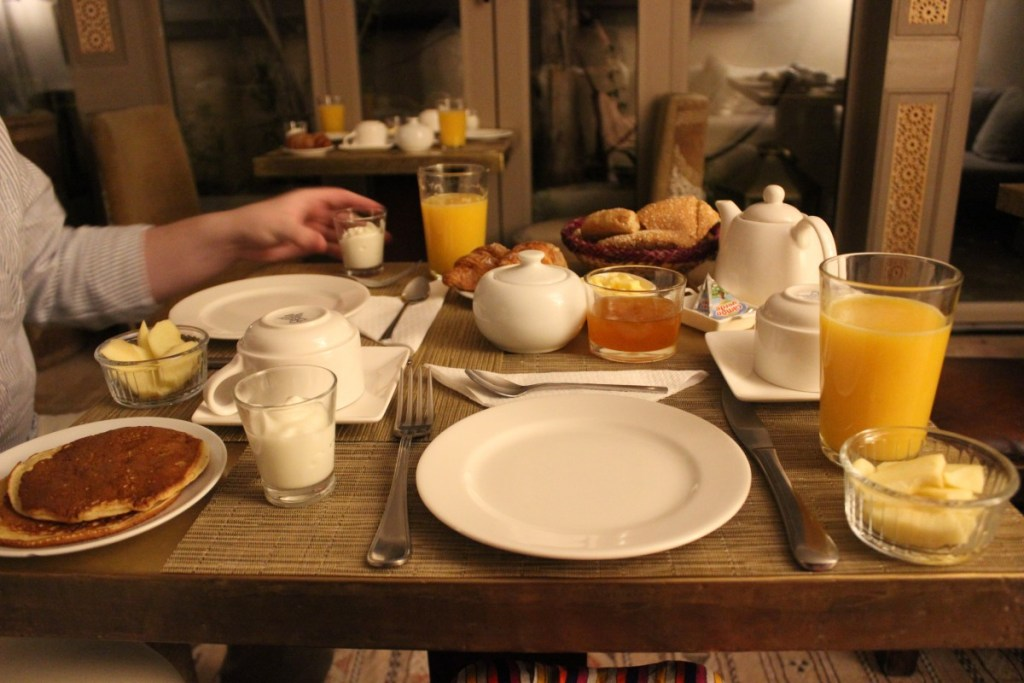 Breakfast at the Riad Anjar, included in the price of the stay. Apples, yogurt, breads, pancakes, juices, and jams sit on a square wooden table, in white ceramic dishes and plates.