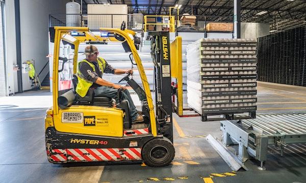 NetSuite-vs-Microsoft-Warehouse-worker-conveyor-belt