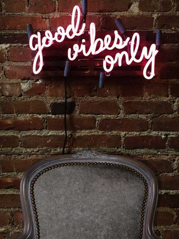 Good Vibes Only neon sign above Rodney Chair