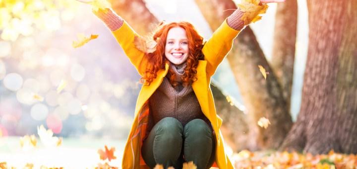 Frau wirft Blätter im Herbst