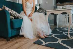 faceless elegant young bride resting on couch before wedding celebration