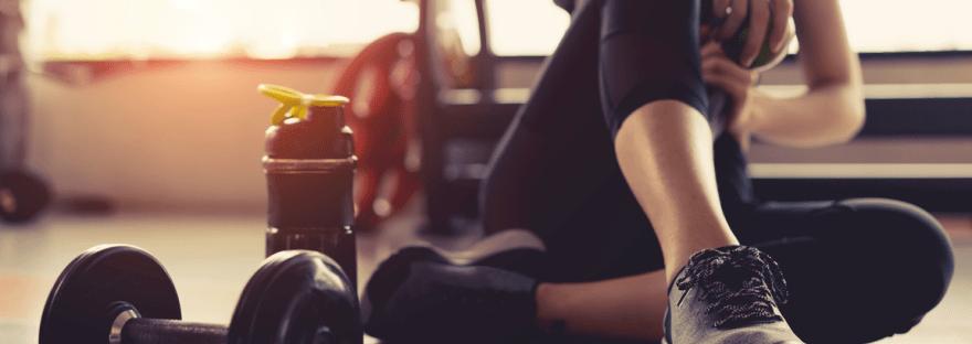 Wie oft trainieren? Frau mit Handtuch über den Schultern, sitzend, Kurzhantel liegt nebenbei