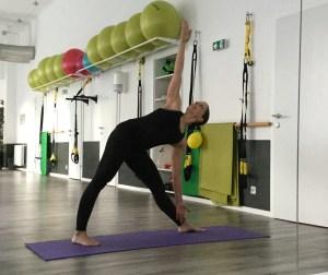 Sportliche Frau macht das Dreieck aus dem Yoga