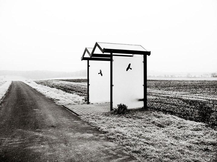 sw-Foto, Straße im Winter mit vereinsamter Bushaltestelle