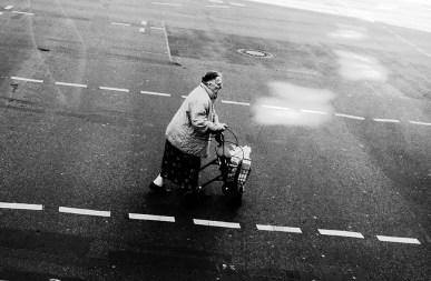 sw-Foto, alte Frau überquert mit Rollator die Straße