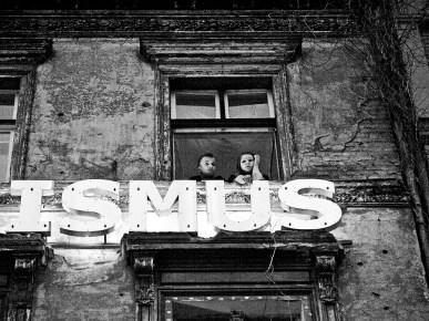 sw-Foto, ein junges Paar schaut aus dem Fenster eines besetzten Hauses