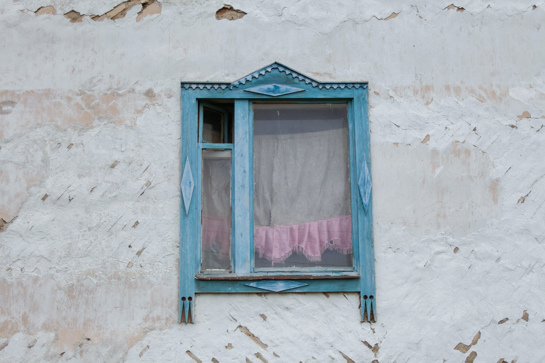 wooden window of weathered rustic house in village