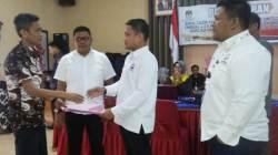 Ketua DPW Perindo Sultra, Jaffray Bittikaka, menyerahkan berkas kepada Komisioner KPU Sultra Iwan Rompo. (Foto: La Ismeid/SULTRAKINI.COM)