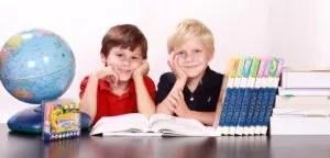 地球儀と本を読む少年2人と本が並んでいる