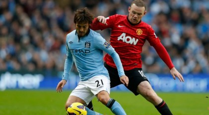 Manchester City's Silva challenges Manchester United's Rooney during their English Premier League soccer match at The Etihad Stadium in Manchester