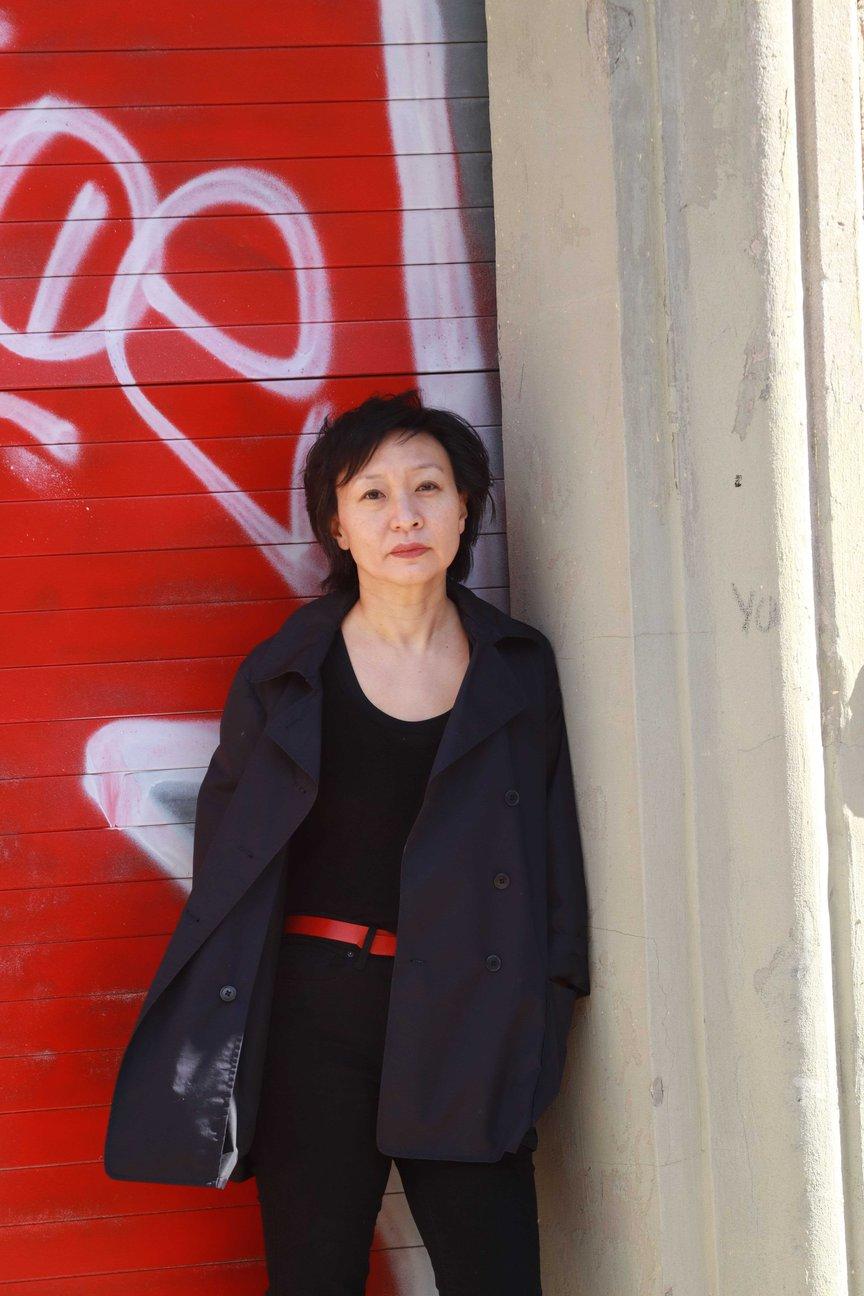 Cathy Park Hong stands in front of a door