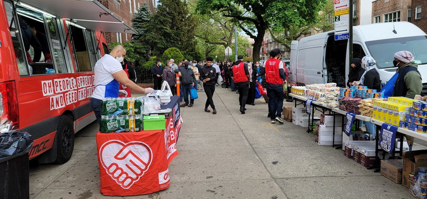 A Muslims Giving Back food truck in a residential neighborhood with volunteers giving food and supplies to people