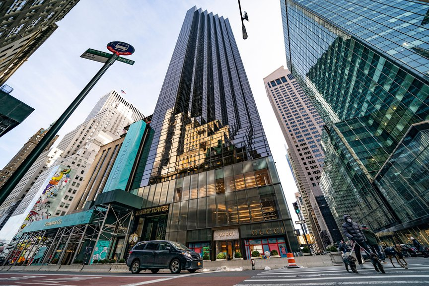 an exterior view of Trump Tower on Fifth Avenue, the dark glassed building with half its tower 'cut out' in a sawtooth fashion
