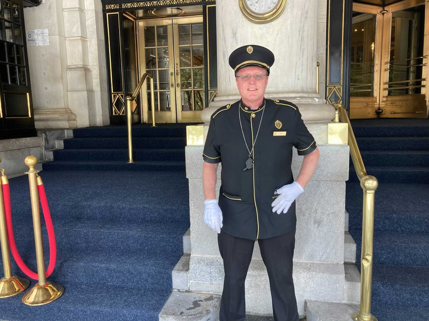 A white doorman stands in his uniform and hat